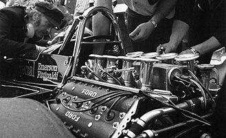 Colin Chapman leans in to talk with Fittipaldi while the crew makes final adjustments.