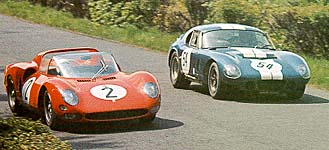 Bob Bondurant (#54 Cobra) and Mike Parkes (#2 Ferrari) race over the scenic 14-mile, 175-corner Nurburgring circuit.