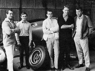 Bob Bondurant, Chris Amon, Jochen Neerpasch, Dan Gurney and Carroll Shelby pose in front of a Cobra coupe during the race preparation in the team garage.