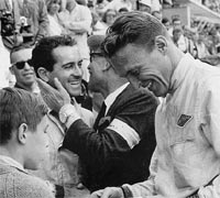 Bob Bondurant receives congratulations while Dan Gurney signs an autograph.